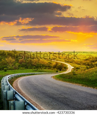 winding road along the green meadows and forests - stock photo