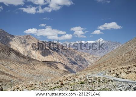 Winding road among desert mountains - stock photo