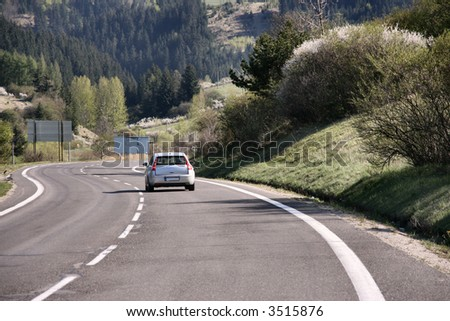 Winding road bends in a rural, desolate, mountain landscape in Europe. - stock photo