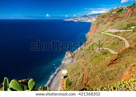 winding road goes down to the beach Ponta do Garajau, Madeira, Portugal - stock photo