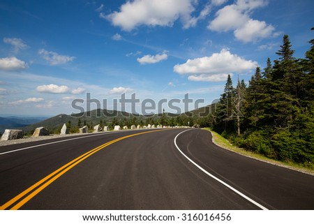 Winding road in Adirondack mountains, upstate New York, USA. Transportation, travel, explore, vacation, summer, destination, driving and nature concept - stock photo