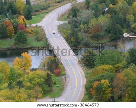 Winding road in fall - aerial view - stock photo