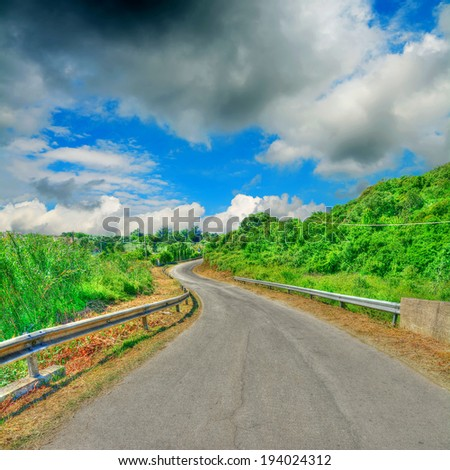 winding road on a cloudy day - stock photo