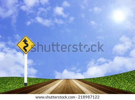 Winding road sign and wood planks floor on blue sky
