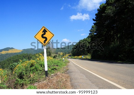 winding road sign, mountain background - stock photo