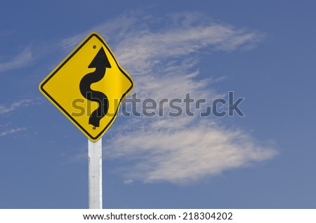 Winding Road Sign with blue sky - stock photo