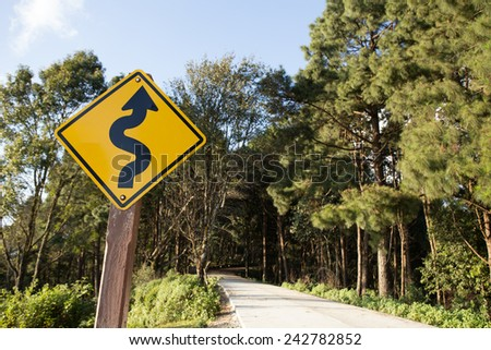 winding road sign,yellow winding road ahead sign in pine wood mountain street - stock photo