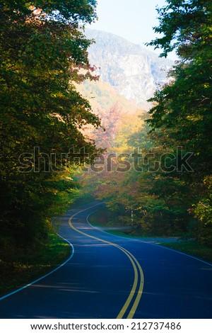 Winding road through autumn trees, Stowe Vermont, USA - stock photo