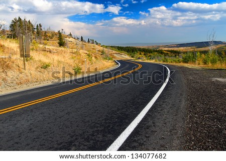 Winding road through the rural countryside of Glacier County Montana - stock photo