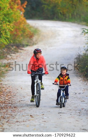 Winding road with mother and child riding bikes together - stock photo