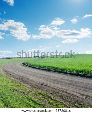 winding rural road under blue cloudy sky - stock photo