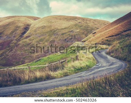 Winding Single Lane Road Up Through The Rugged Landscape Of The Scottish Borders