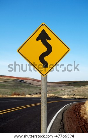 Winding traffic sign winding road on background - stock photo