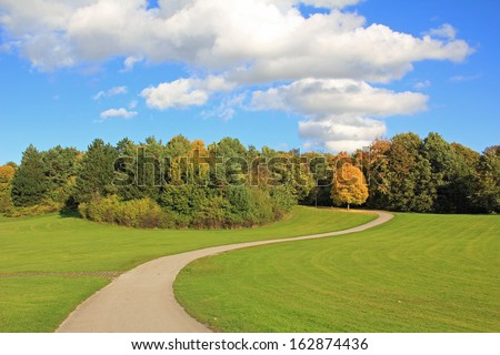 winding walkway in autumnal park landscape - stock photo
