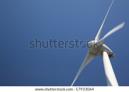 Windmill against blue sky with motion in blades - stock photo