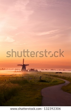 windmill and horses on summer pasture at sunrise, Groningen - stock photo