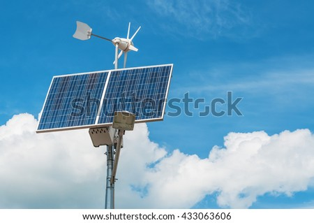 windmill and solar panel against the blue sky