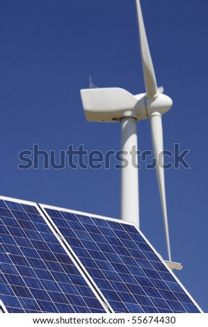 windmill and solar panel with a clear blue sky - stock photo