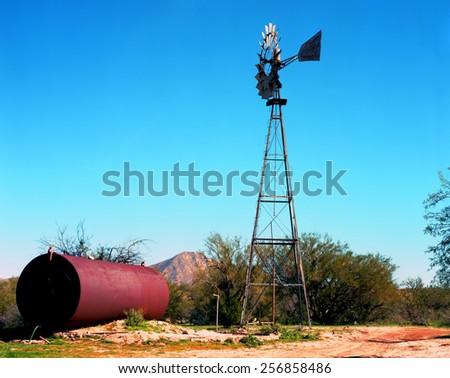 Windmill and storage in the Arizona desert - stock photo