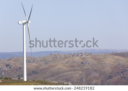 Windmill at windfarm - renewable electric energy production - stock photo