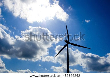 Windmill conceptual image. Close up of a windmill against the blue sky. - stock photo