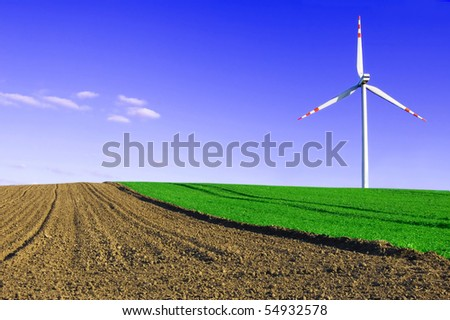 Windmill conceptual image. Windmill on the green and plowed field. - stock photo