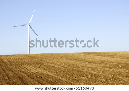 Windmill conceptual image. Windmill on the plowed field. - stock photo