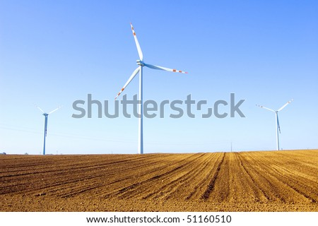 Windmill conceptual image. Windmills on the plowed field. - stock photo