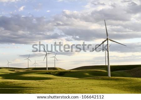 Windmill farm taken at sunset on rolling farm land. - stock photo