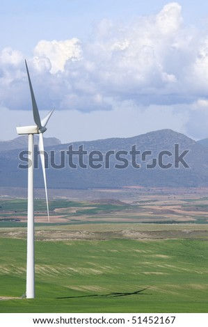 windmill in a landscape of mountains and meadows with cloudy sky - stock photo
