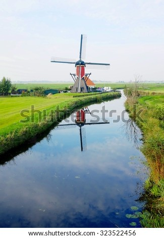 Windmill in a rural  setting reflecting in the water - stock photo