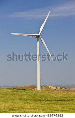 Windmill in green field over cloudy sky - stock photo