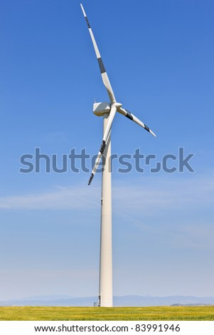 Windmill in green field over cloudy sky