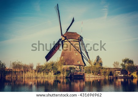 Windmill in Kinderdijk, beautiful landscape with sky, trees and reflection in the water, Netherlands. Nature hipster vintage background - stock photo