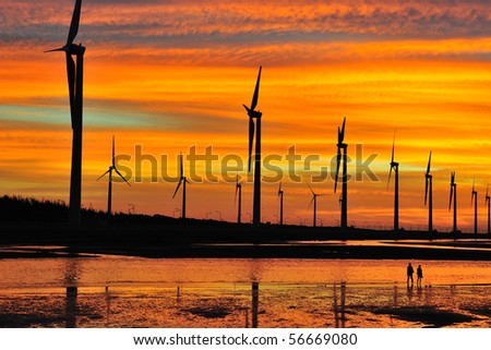 windmill in sunset at seacoast - stock photo