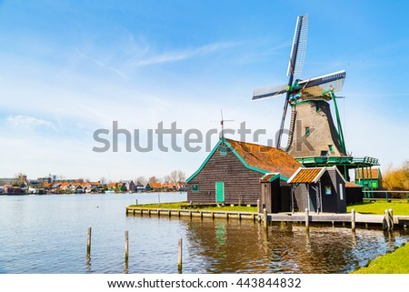 Windmill in Zaanse Schans, traditional dutch village in Netherlands, North Holland and reflection in the water - stock photo