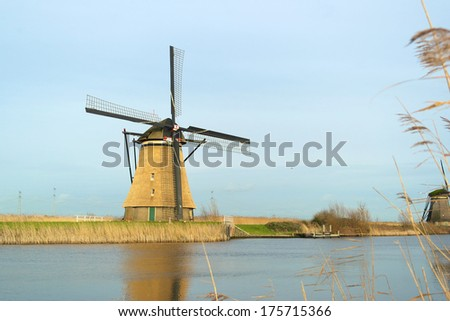 Windmill landscape in the winter at Kinderdijk (the Netherlands), with beautiful reflection in the water. - stock photo