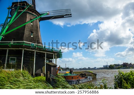 Windmill on a river with a boat.  The Netherlands.  Holland. - stock photo