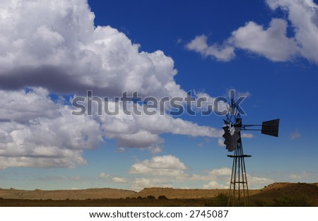 Windmill on bright blue sky background with white puffy clouds in the Karoo, South Africa. - stock photo