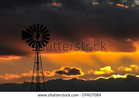 Windmill over impressive sunset - stock photo