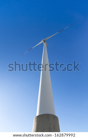 windmill Pinwheel wind turbine wind farm on a cement pillar with blue sky