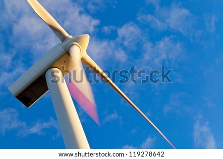 Windmill power generator at sunset with blue sky