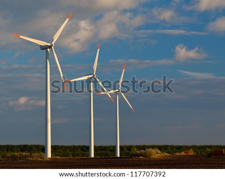 Windmill power generators at sunset with blue sky