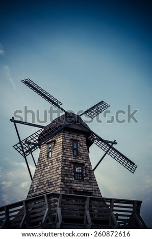Windmill standing in the blue sky creating a nice aerial view in dark vintage color - stock photo