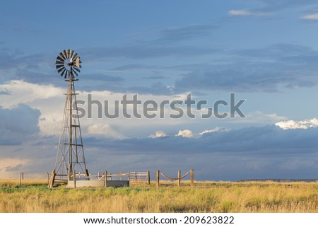 windmill with a pump  and cattle water tank in shortgrass prairie, Pawnee National Grassland in Colorado near Grover - stock photo
