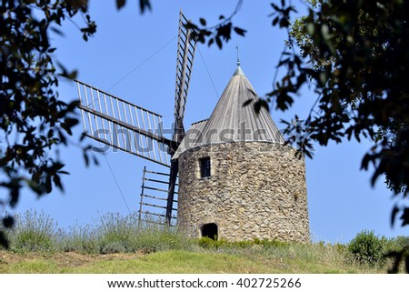 Windmill with foliage tree at Grimaud, commune in the Var department in the Provence-Alpes-Cote of Azur region in southeastern France
