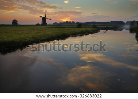 Windmill with sunset reflected in water in the Netherlands - stock photo