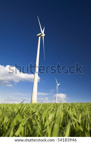 Windmills against a blue sky and clouds, alternative energy source - stock photo