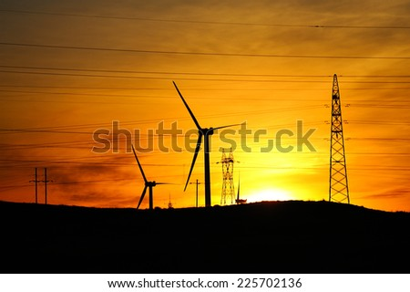 windmills and electric transmission towers at dusk. - stock photo