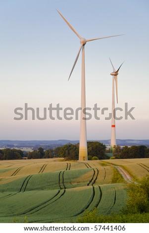 Windmills at dusk, an alternative energy source - stock photo